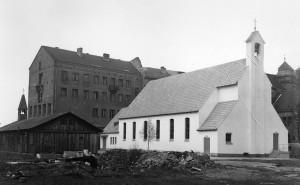 Zwei Kreuzkirchen nebeneinander: Am Ort der heutigen Kreuzkirche steht 1950 noch die Schweizer Militärbaracke, die als Notkirche diente - daneben die am 16. April 1950 eingeweihte »Bartning-Notkirche«. Im Hintergrund ist das Pfarrhaus mit notdürftig repariertem Dachstuhl zu sehen.